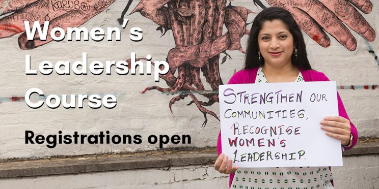 Woman holding a sign saying 'Strengthen our communities, recognise women's leadership'