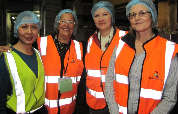 Four women in a factory standing in high-vis jackets and hair nets