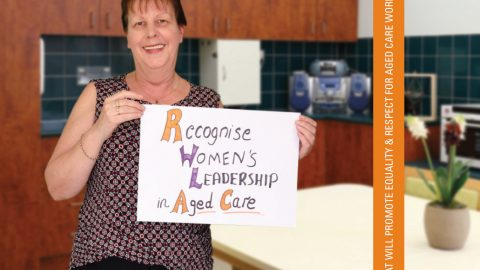Image of a migrant woman working in aged care holding a sign that reads 'Recognise Women's Leadership in Aged Care'