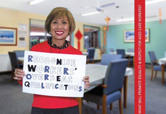 Image of a smiling migrant woman working in aged care holding a sign that reads 'Recognise Workers' Overseas Qualifications'