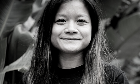 A young woman with long hair outside in the sunshine wearing a T shirt and facing the camera