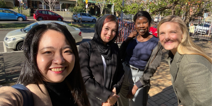 Four women standing outside on a sunny day with dappled light behind a car lined street. They are smiling at the camera.