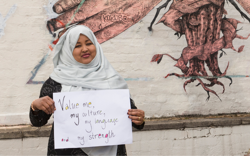 Woman with a beautiful smile in a light grey hijab holding a sign that reads 'Value me, my culture, my language and my strength'