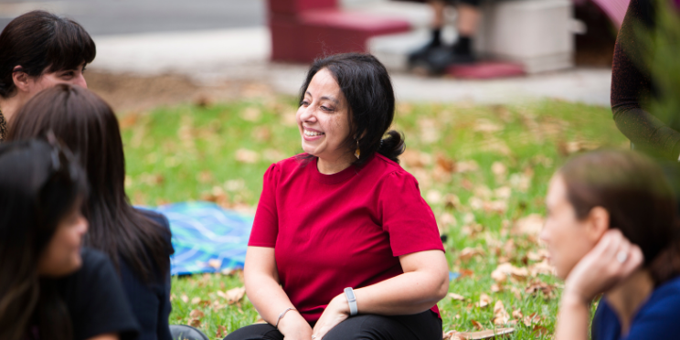 A woman, Monisha from MCWH, sitting on a picnic blanket on the lawn, smiling widely. There are other women sitting on the lawn around her. It's a bright day.