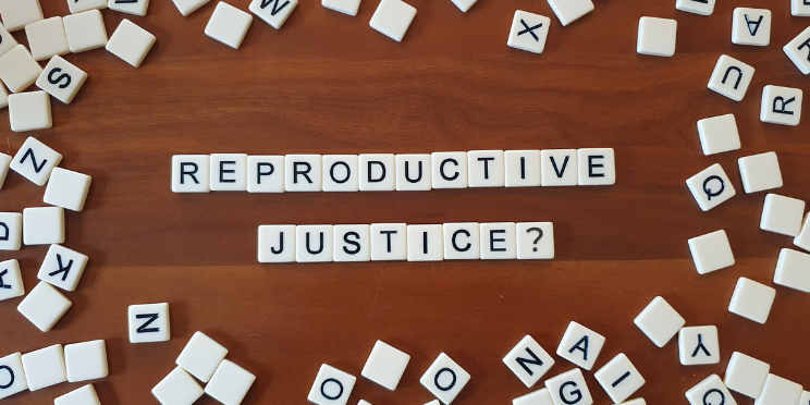 Scrabble tiles on a wooden table form the words 'reproductive justice?'